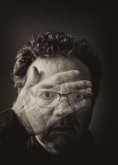 Double exposition photo. man closed his face with hand. schizophrenia or bipolar disorder concept