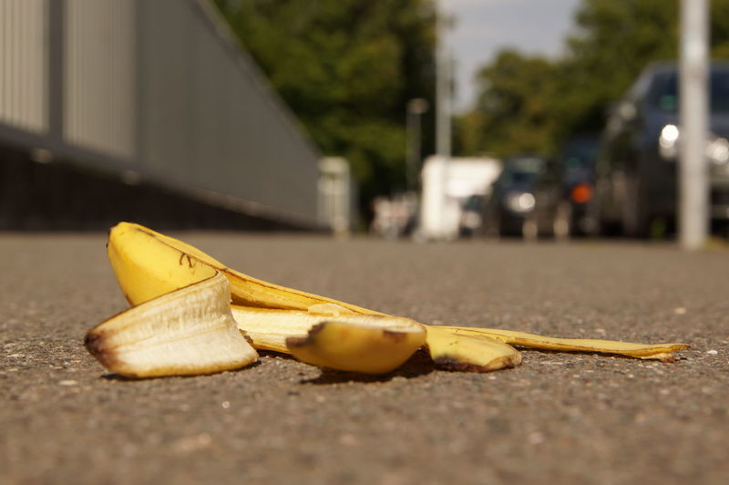 Accident Waiting To Happen Asphalt Background Banana Banana Peel Banana Skin Close-up Copy Space Danger Focus On Foreground Footpath Ground Hazard No People Outdoors Selective Focus Sidewalk Slipping On Banana Peel Surface Level