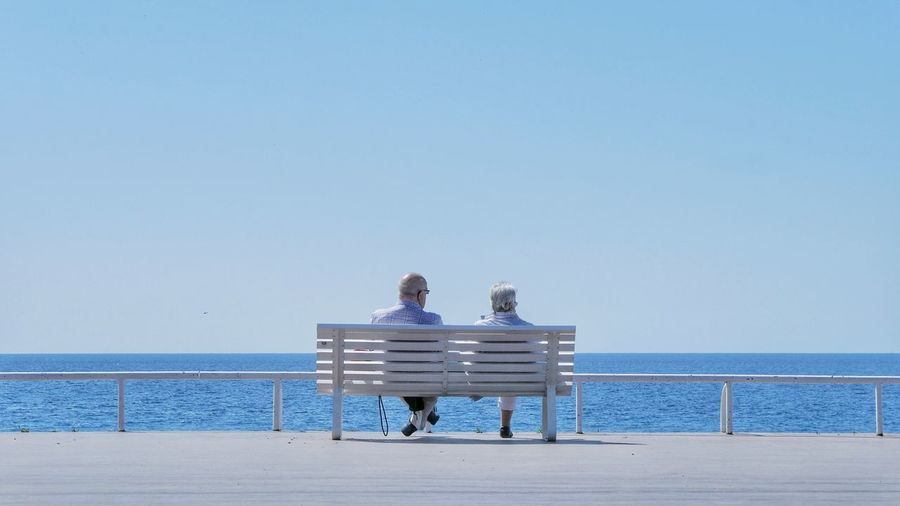 Rear view of woman sitting on beach against clear blue sky