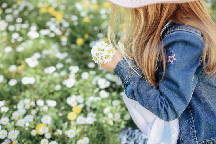 Plant One Person Blond Hair Flowering Plant Flower Hair Casual Clothing Day Long Hair Leisure Activity Nature Child Hairstyle Holding Focus On Foreground Lifestyles Freshness Outdoors Jeans Daisy Picking Flowers  Picking Sunshine Springtime Spring