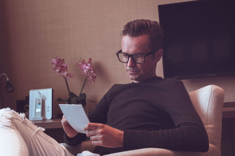 Sitting Eyeglasses  One Person Lifestyles Home Interior Men Real People Working Taking Notes Writing To Do List Businessman Business Casual Males  Armchair Home Office Serious Entrepreneur Working From Home Indoors  Glasses