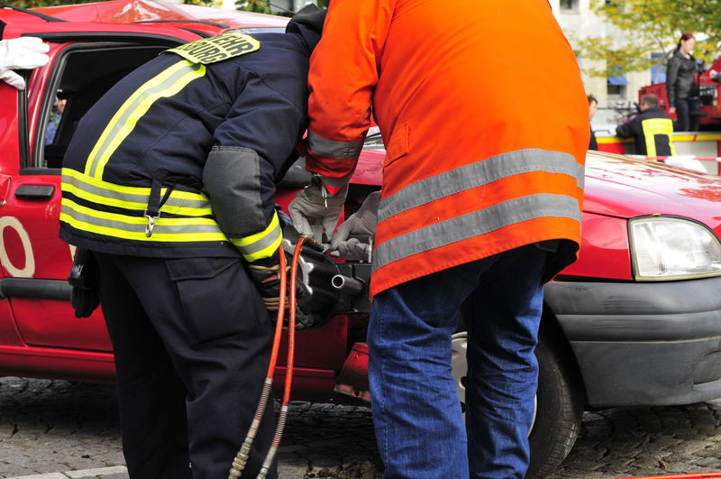 Fire brigade opens a car with rescue shears in the event of an accident Mode Of Transportation Occupation Transportation Accidents And Disasters Safety Healthcare And Medicine Protection Real People Land Vehicle Firefighter Rescue Worker Men Teamwork Emergency Services Occupation Two People Rescue Cooperation Protective Workwear Security Fire Hose Uniform