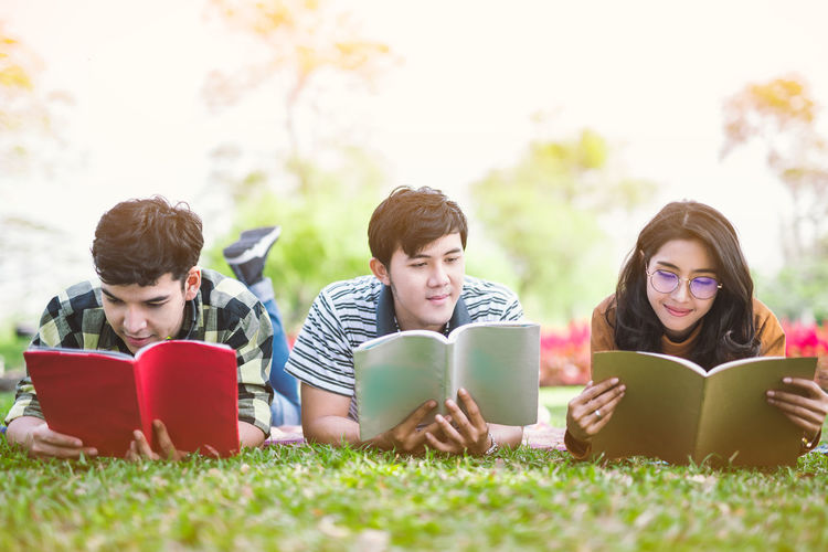 Friends reading books while lying down on field at park