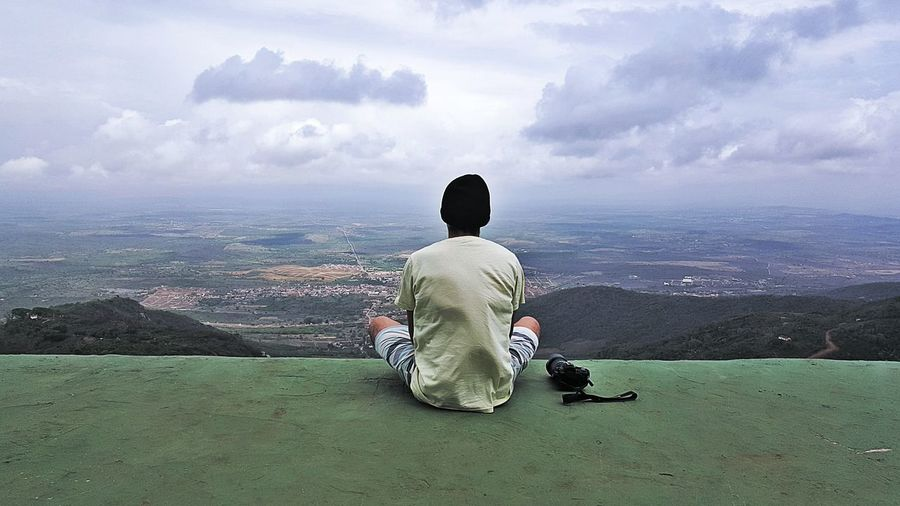 Rear View Of Man By Camera Sitting At Observation Point