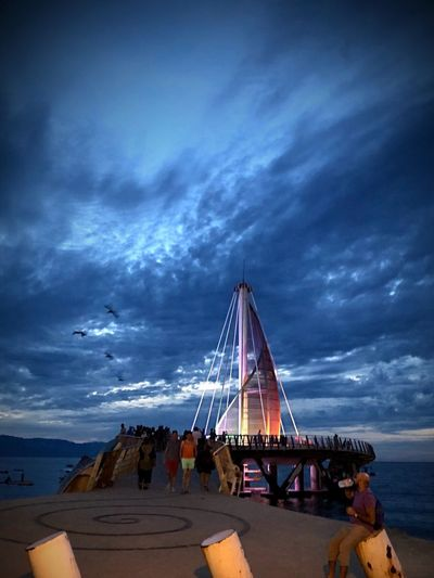 Puerto Vallarta Shotonphone Mexico Travel Lighted Up Bridge Sunset Blue Clouds Playadelosmuertos #puertovallarta #mexico #iphonexgraphy #iphonephotography Sky Cloud - Sky Built Structure Architecture Outdoors Beach Nature Water Large Group Of People Real People Horizon Over Water Sea Day Mobility In Mega Cities Mobility In Mega Cities