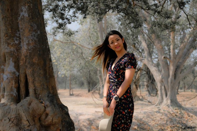 Portrait of smiling woman standing amidst trees in forest