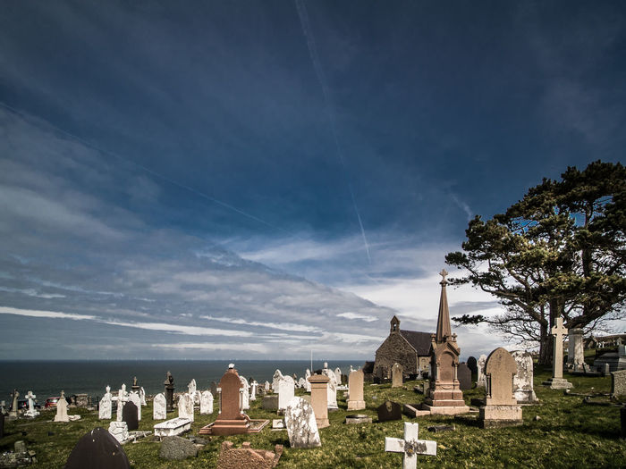 Cemetery by sea against sky