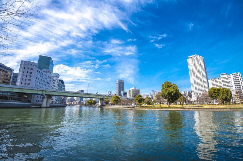 River by modern buildings against blue sky