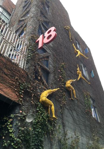Abstract Yellow Figures and Number 18 on Building - Shenzhen, China kArtistic cYellow People eFigures sPeople eUrban nUrban Street Art tUrban Art tChina aShenzhen nBrick Wall lStreet Art tArt tBuilding gExterior rInstallation Art tFigures sEighteen  n18 8Number Eighteen nNumber 18 8Red Number r