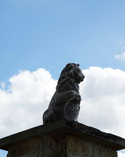 A lion standing against sky Lion King  With A Trophy On His Pillar Statue Paw Of Feline On Pillar Against Sky Format 4x5