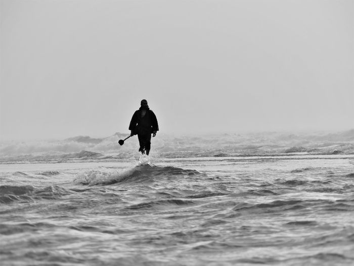 Man at sea against sky