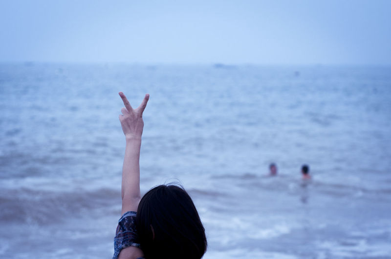 Woman hand by sea against sky