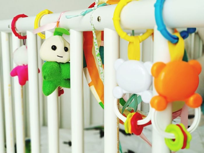 Close-up of toys hanging in crib at home