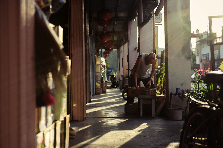 An old man works hard in his golden age for living in a small town somewhere in Behrang Stesen, Perak. Architecture Built Structure Casual Clothing Chinese City City Life Day Flare Leisure Activity Lifestyles Malaysia Old Man Outdoors People People Photography Shadow Shopkeeper Vintage Working Working Hard