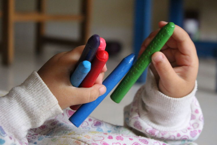 Midsection Of Child Holding Colorful Crayons While Lying At Home