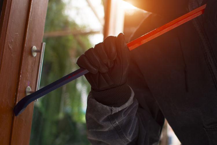 Midsection of burglar breaking door with crowbar
