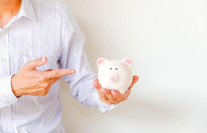 Young man holding and pointing finger to a piggy bank, Space for text Adult Attractive Background Bank Banking Business Businessman Cash Casual Caucasian Color Deposit Economy Emotional Executive  Finance Financial Finger Formal Handsome Happy Holding Investment Male Man Money People person Pig Piggy Pointing Portrait Save Savings Showing Smile Space Success Successful Text Wealth White Worker Young