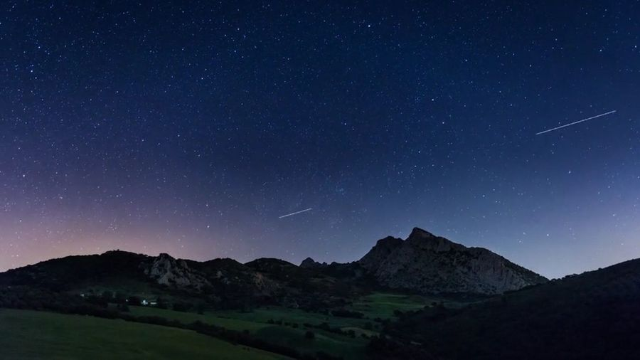 Scenic view of mountains against starry sky at night