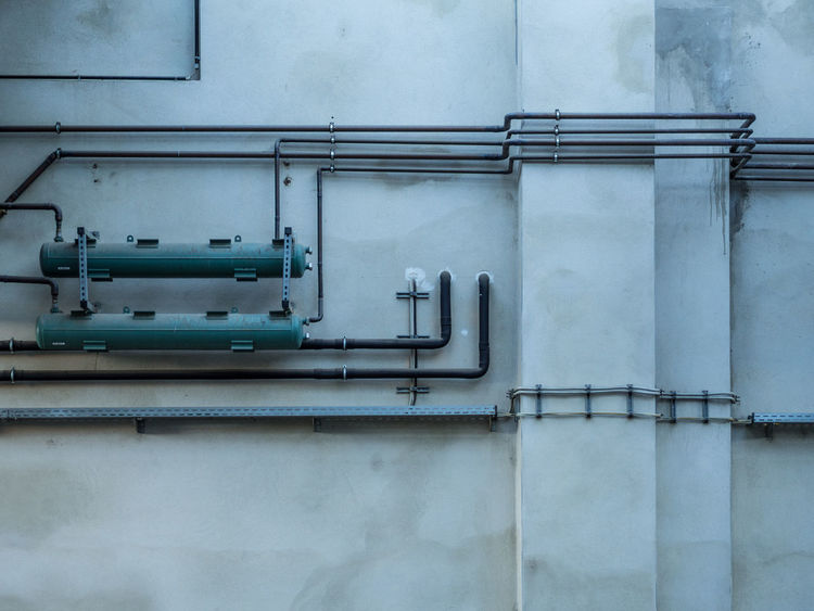 Architecture No People Built Structure Building Exterior Wall - Building Feature Metal Day Railing Pipe - Tube Outdoors Close-up Factory Industry Backgrounds Connection Pipeline Building Roadmap Concrete Concrete Wall Heating Water Pipe Pattern Pipe Industrial Building  Exterior Mounted