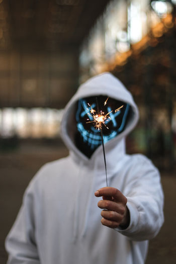 Man wearing mask and hood while holding illuminated sparkler