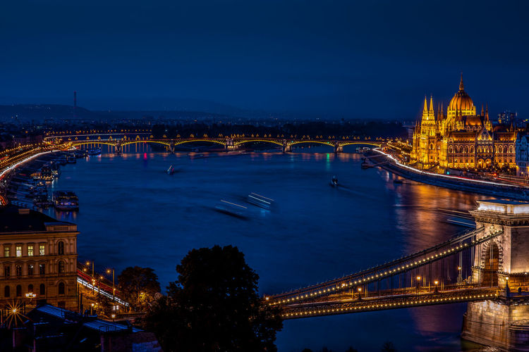 Illuminated bridge over river at dusk