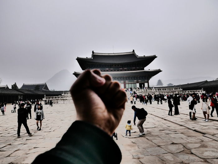 Cropped image of man fist by gyeongbokgung against clear sky