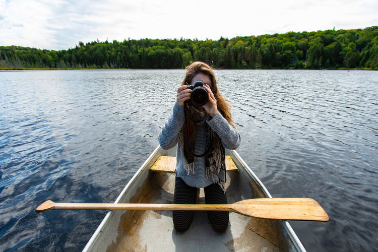 Man photographing while standing on lake