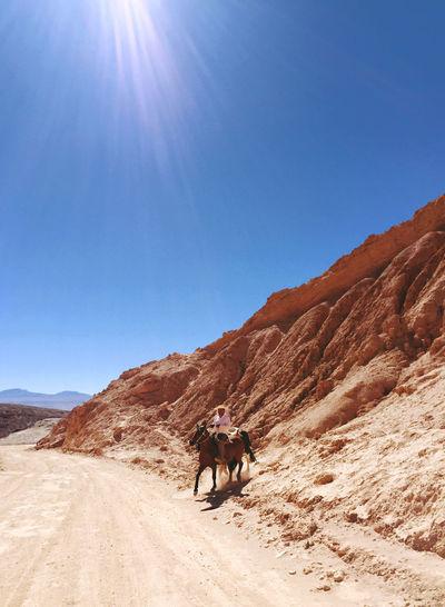 Man Riding Horse Against Rock Formation At Atacama Desert