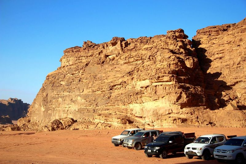 Cars on rock formation against clear sky