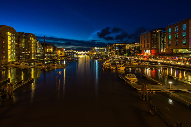 Night cityscape of modern buildings in Trondheim along Nidelva river, Norway Trondheim Norway Scandinavia Norwegian Northern Europe Night Illuminated Building Exterior Architecture Built Structure Reflection Water City No People Sky Building Nature Dusk Outdoors Transportation Residential District Waterfront Cloud - Sky Long Exposure Canal
