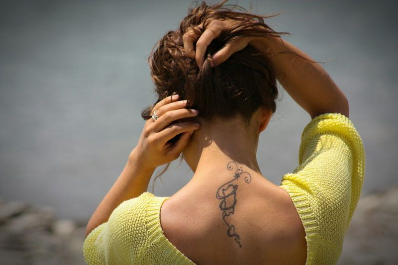 Rear view of woman with tattoo on her back