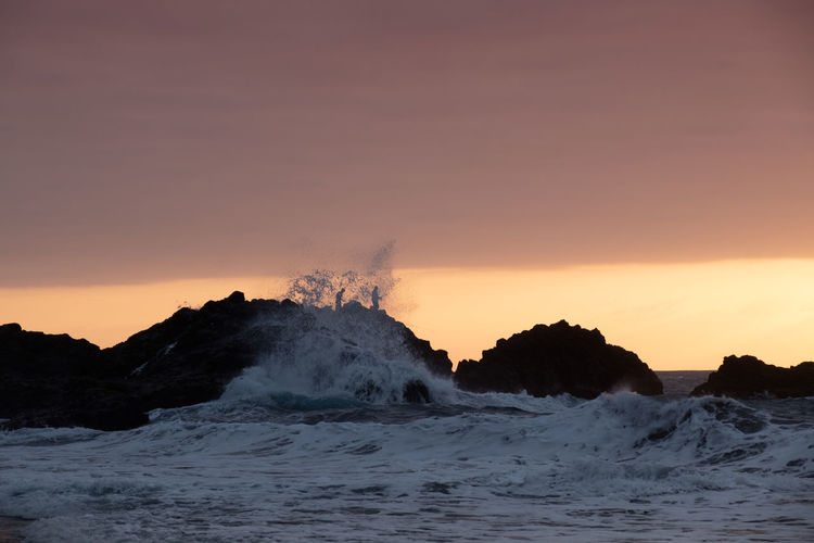 Sunset at bollullo beach at tenerife island with huge breaking waves.