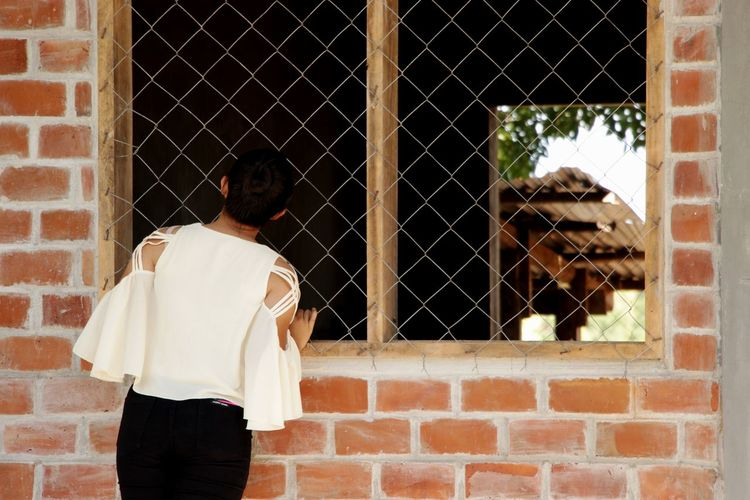 Rear view of a woman looking through window