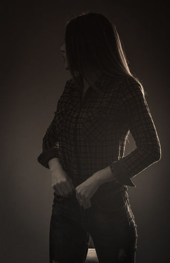 Rear view of woman standing against black background