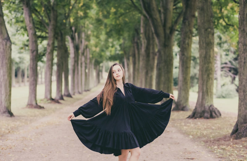 Young woman wearing dress standing in park
