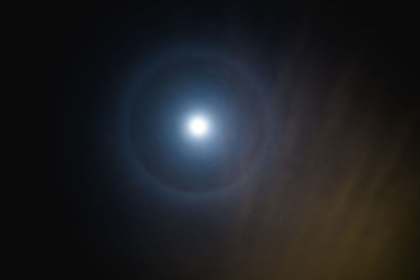 Full moon with halo of light surrounding in dark night sky. Night Astronomy Space Sky Moon No People Star - Space Illuminated Nature Full Moon Single Object Science Moonlight Natural Phenomenon Beauty In Nature Outdoors Galaxy Light - Natural Phenomenon Dark Solar Eclipse Eclipse Astrology Bright Luminosity