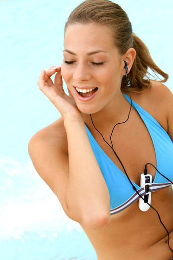 young blond woman listening to music with MP3 players at the pool Beautiful Happy Holiday Listening Music Music Summer Holidays Woman Beautiful Woman Bikini Blond Girl Happyness Leisure Leisure Activity Lifestyles Mp3 Player One Person Pretty Relaxation Smiling Swimming Pool Vacation Water Wellbeing Young Adult