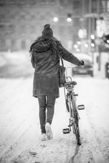 Rear view of person riding bicycle on road in winter