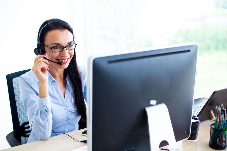 Smiling female call center worker with headset