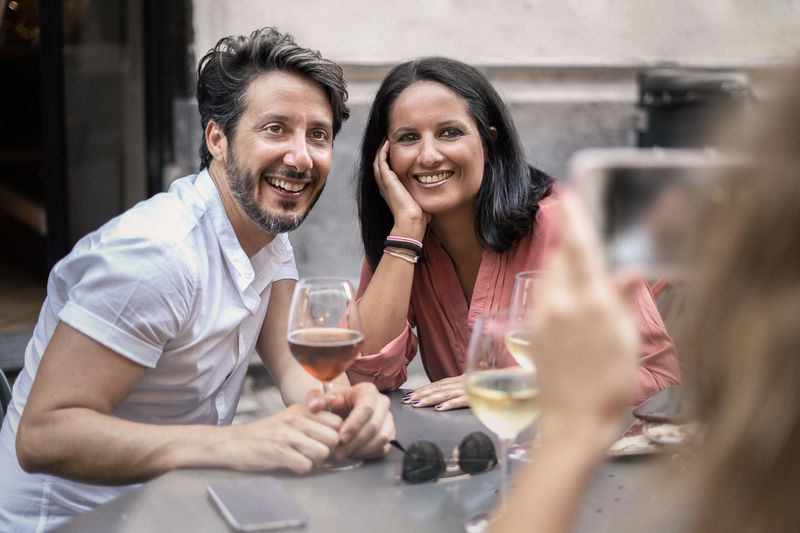Woman Photographing Smiling Friends At Restaurant
