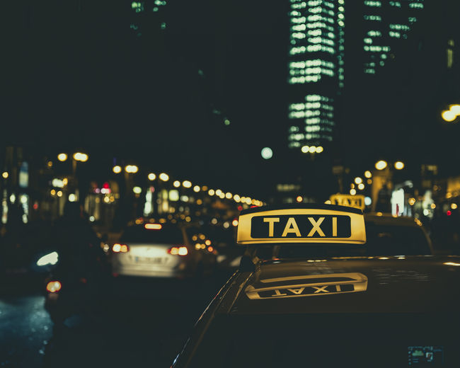 Illuminated taxi text on car roof in city at night