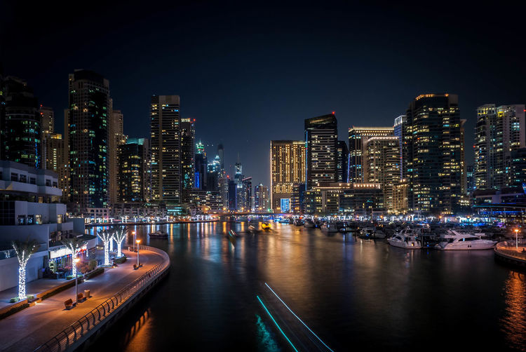Boats Moored At Marina By Illuminated Cityscape At Night