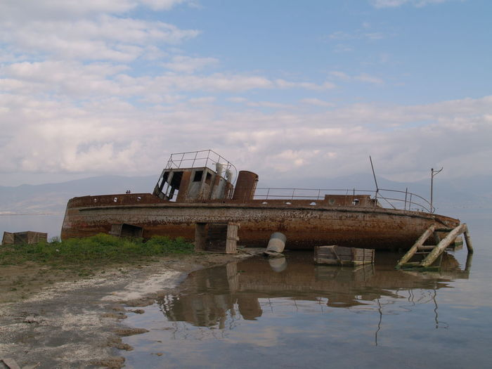 Abandoned boat in lake against sky