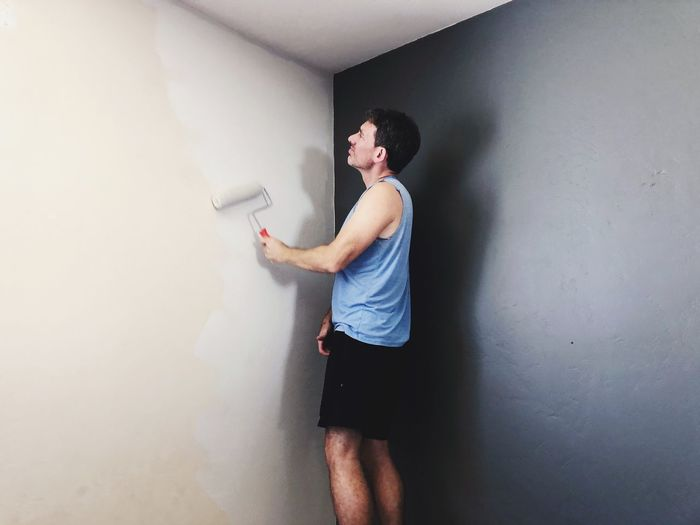 Side view of man painting on wall at home