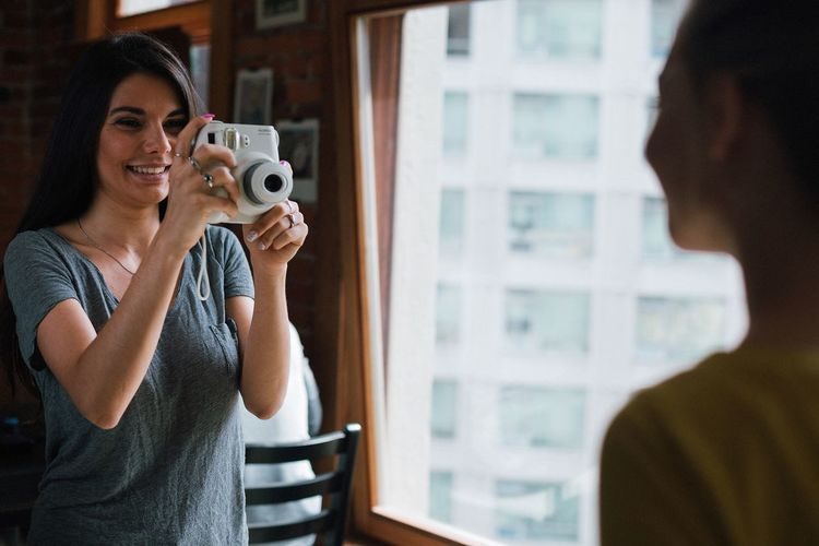 Camera - Photographic Equipment Enjoyment Friendship Indoors  Leisure Activity Only Women People Photographing Photography Themes Real People Smiling Standing Togetherness Women Young Adult Young Women
