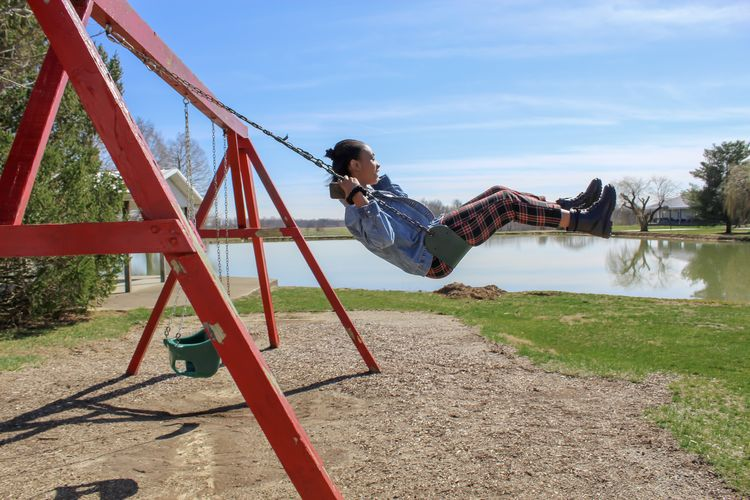 Rear view of teenager girl swinging in playground against sky