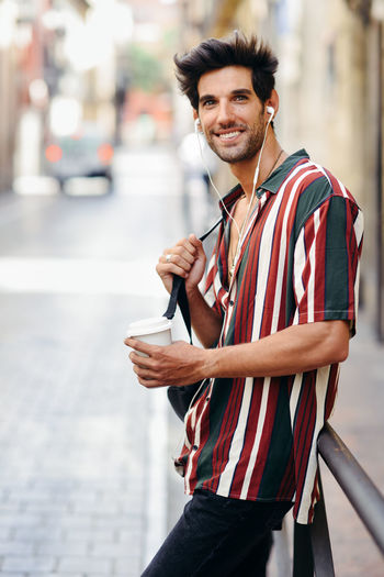 Portrait of happy man having coffee while standing by railing in city