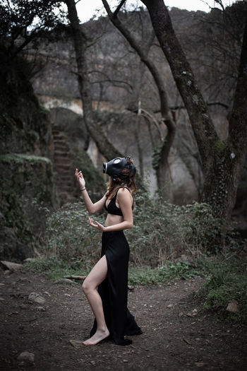 Full length of young woman wearing gas mask standing at forest