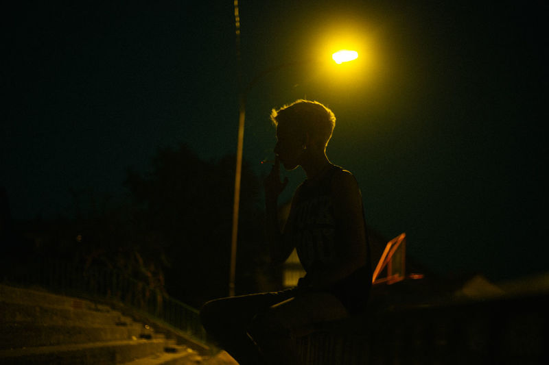 Silhouette woman smoking cigarette while sitting on railing against illuminated street light at night