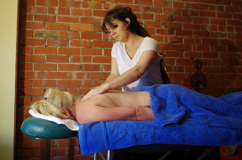 Massage Therapist Rubbing Back Of Senior Woman At Health Spa